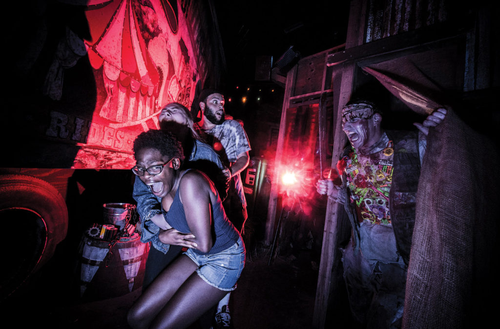 Two women and a man (guests) crouching and running in fear as a scare actor (right) pops out inside of a Haunted House at Universal Studios® Halloween Horror Nights, Orlando, Florida.