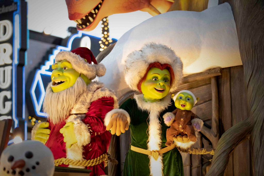 Shrek (left) and Princess Fiona (right) dressed as Mr and Mrs Claus while Fiona holds their baby on a Christmas float as part of the Macy's Christmas Day Parade in Universal Studios Florida.