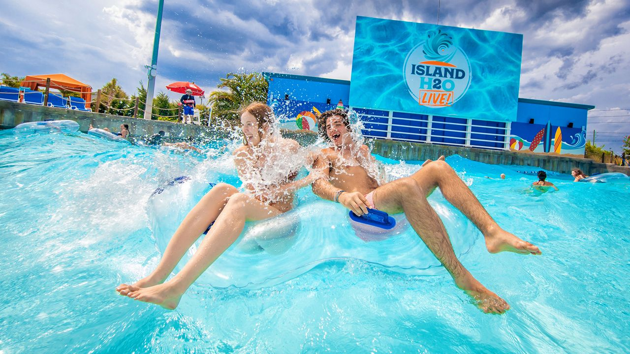 Girl (left) and guy (right) in double tube at the Island H2O Live! wave pool. Daytime shot. Kissimmee, Florida.