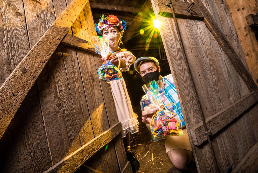 Female (left) and male (right) dressed in costume in a barn holding goodie bags of Halloween candy for The Haunted Road's daytime family-friendly drive-in event. 2020. Orlando, Florida.